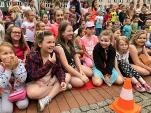 tłum dzieci Crazy Kids siedzący na Rynku z uśmiechniętymi buźkami