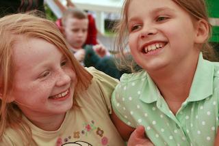 Dziewczyny siedzą i uśmiechają się