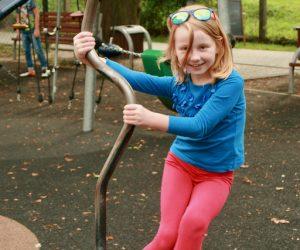 Dziewczynka w niebieskiej bluzce bawi się na plan zabaw