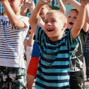 chłopcy na spotkaniu dla dzieci śpiewają i machają rękami