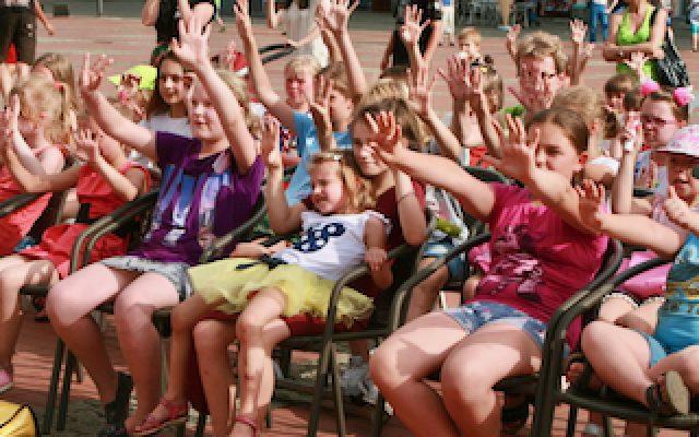 Tłum dzieci siedzący na krzesłach z wyciągniętymi palcami do góry