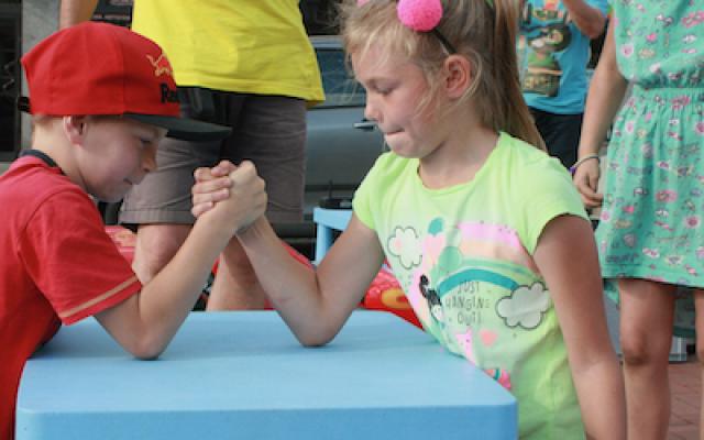 Na Crazy Kids chłopak siłuje się na ręce na plastikowym stole